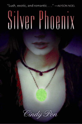 book cover showing a close-up of a glowing green pendant being worn by a person of indeterminate ethnicity
